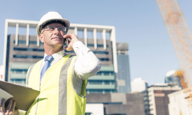 Senior engineer man in suit and helmet talking mobile phone